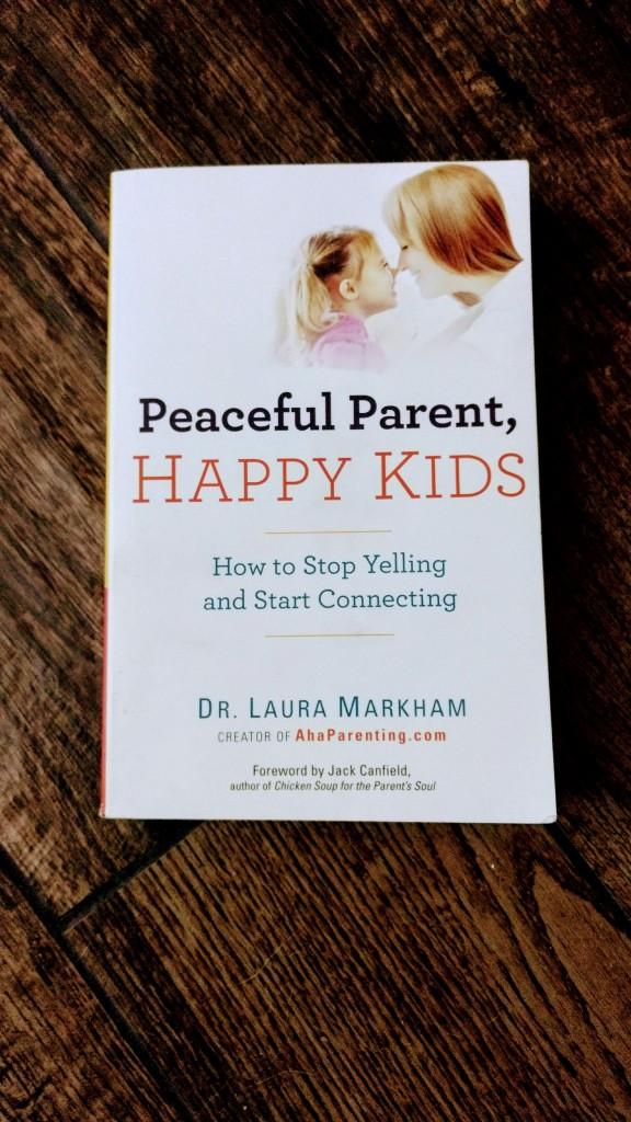 """""""Peaceful Parent, Happy Kids"""" book on hardwood floor"""