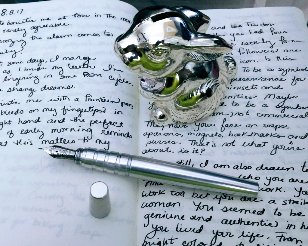 silver fountain pen resting on a journal with cursive handwriting